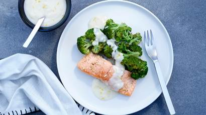 Roasted salmon and broccoli with lemon Parmesan sauce on a white plate with a blue napkin