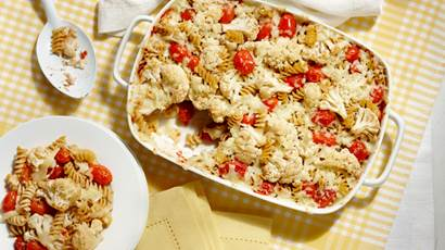 Roasted tomato and cauliflower pasta bake in a white rectangular casserole dish on a white and yellow