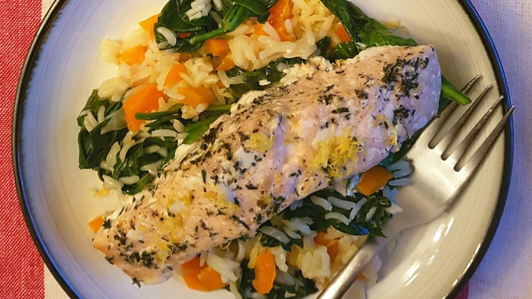 Plate of cooked salmon, spinach, carrots and rice