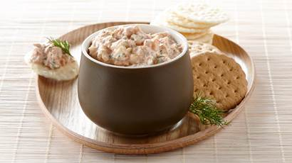 Salmon yogurt spread in a small bowl, served on a wooden plate with an assortment of crackers