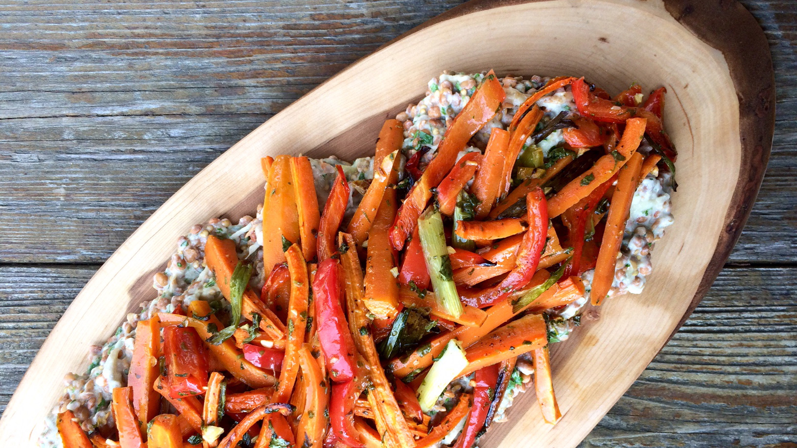 Shredded roasted carrot and eggplant overtop lentils served in wooden platter