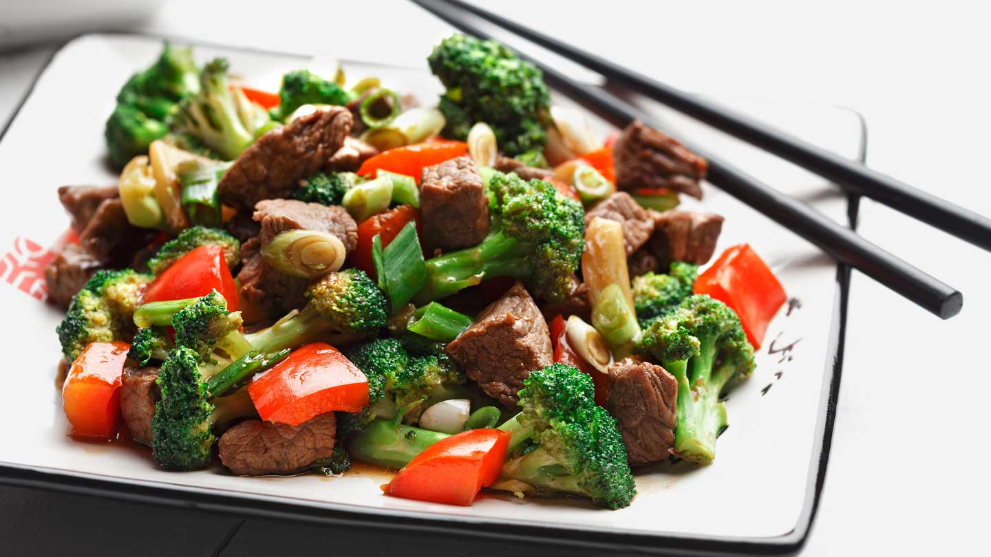 Stir fried broccoli  red peppers and beef on a white plate with chopsticks