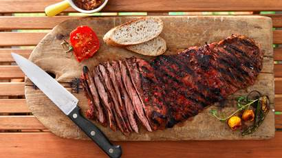 Yucatan spiced skirt steak on a wooden board with a knife