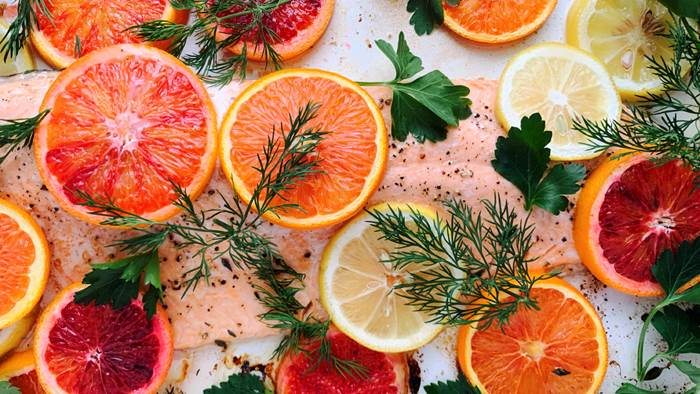 A fillet of salmon covered with citrus slices and herbs