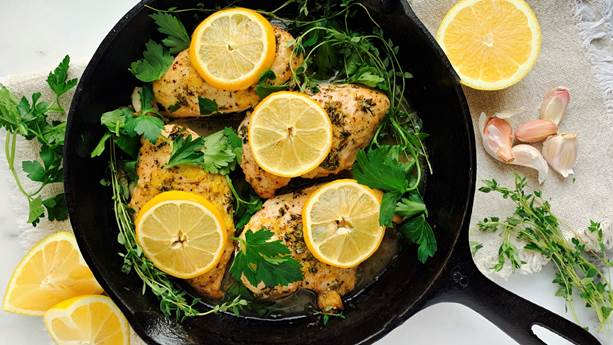 Chicken breasts and lemon slices in a black skillet