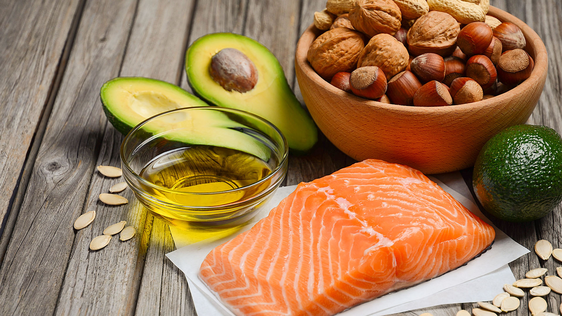 Selection of healthy fat sources: salmon, nuts, seeds, avocados and olive oil.