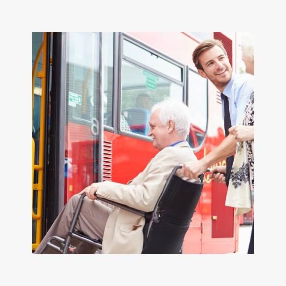 Driver helping senior couple board a bus via wheelchair  ramp