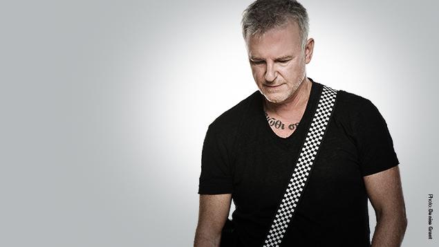 Singer Alan Frew, a stroke survivor, holds a guitar.