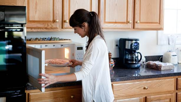 Woman in kitchen using a microwave