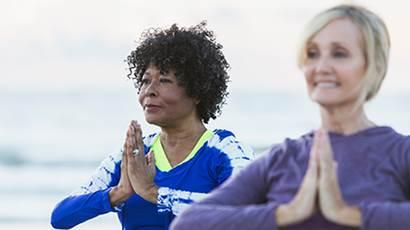 Two women doing beach yoga