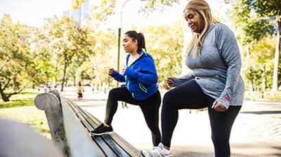 Two women doing lunges on the park bench