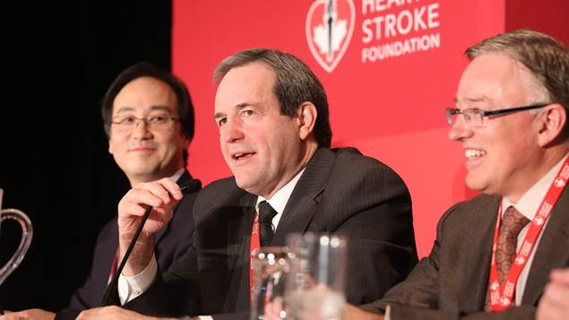 Three male speakers sit at a table with a microphone in front of a red panel.