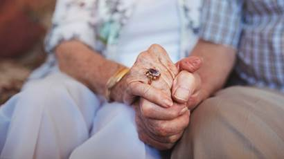 Cropped shot of elderly couple holding hands while sitting together at home