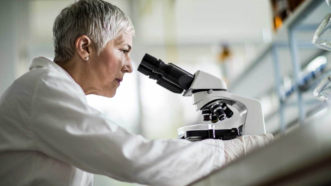 Female researcher using microscope in lab