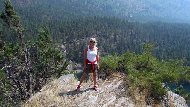 Sandra Thornton stands on a rocky hilltop surrounded by forest.