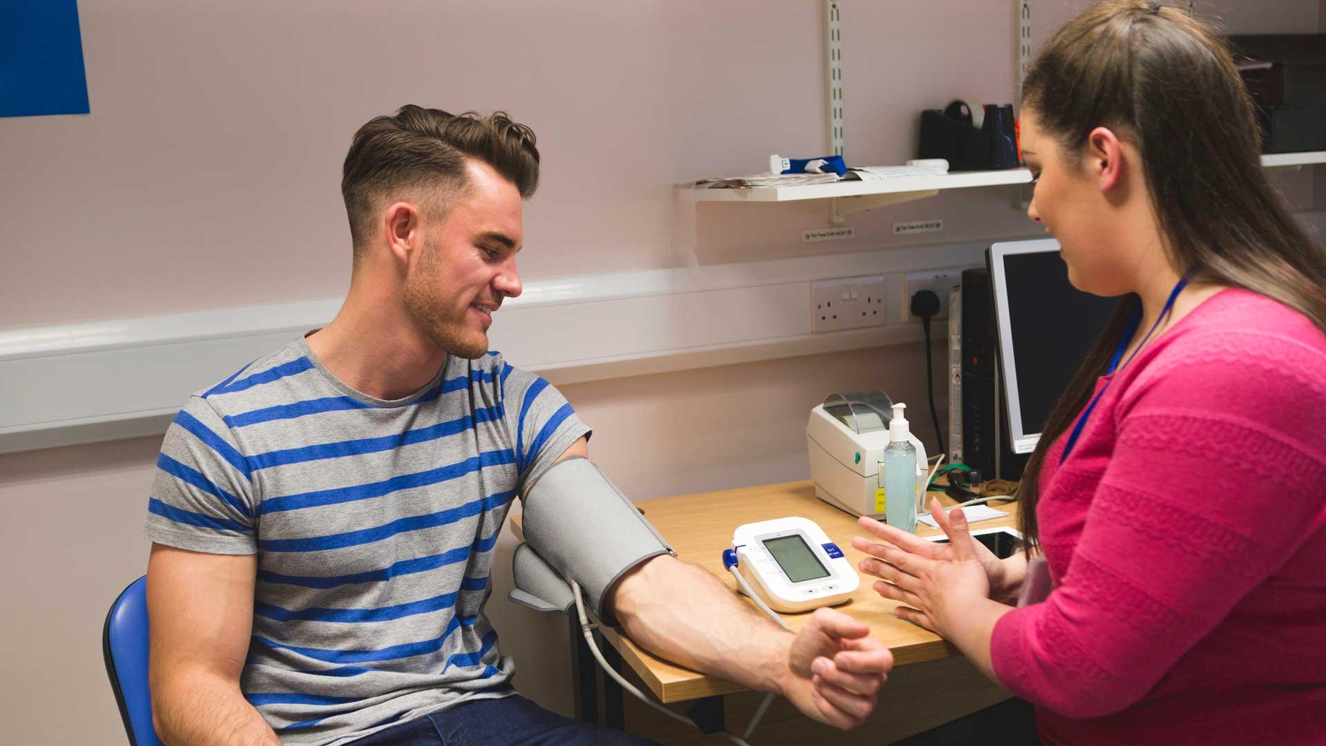 Nurse taking mans blood pressure