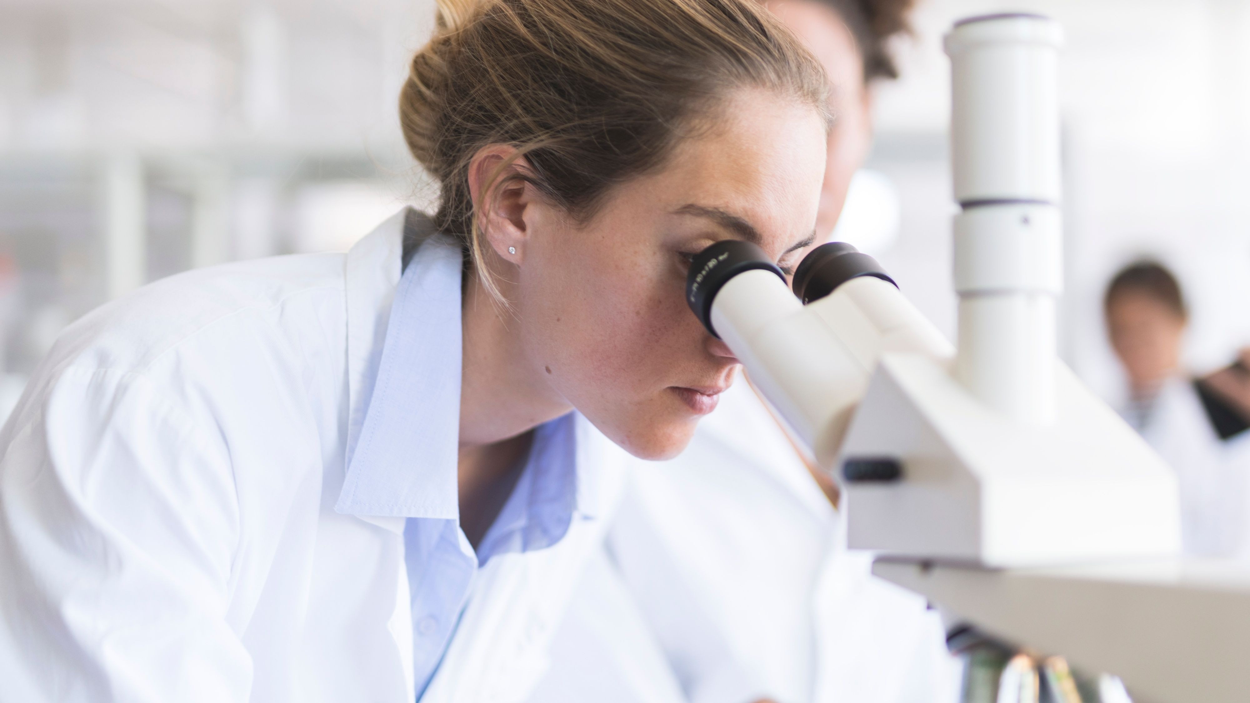 woman looking through a microscope.