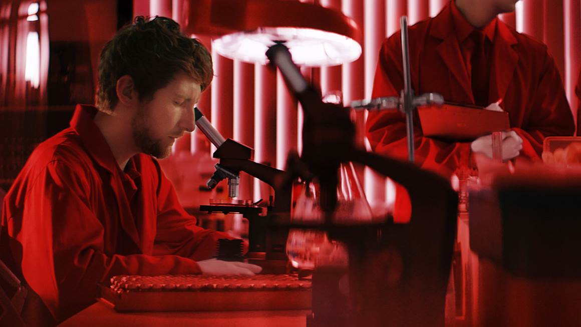 Scientist looks in a microscope against a red background.
