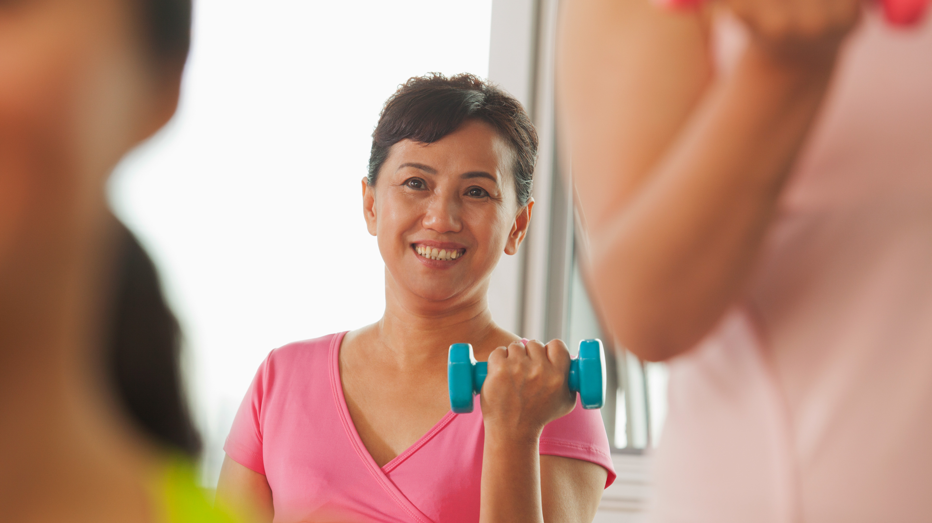 mature woman lifting weights in gym