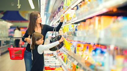 Mom and young daughter shopping in dairy aisle of supermarket.