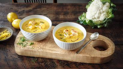 Cauliflower soup in two white bowls placed on wooden cutting board