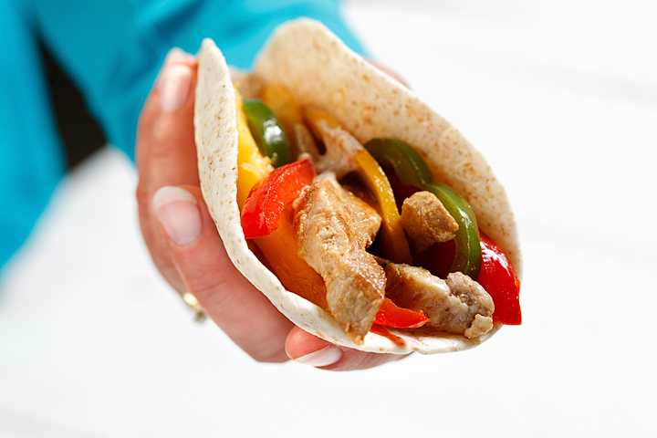 Pork fajitas with mango held in a hand.