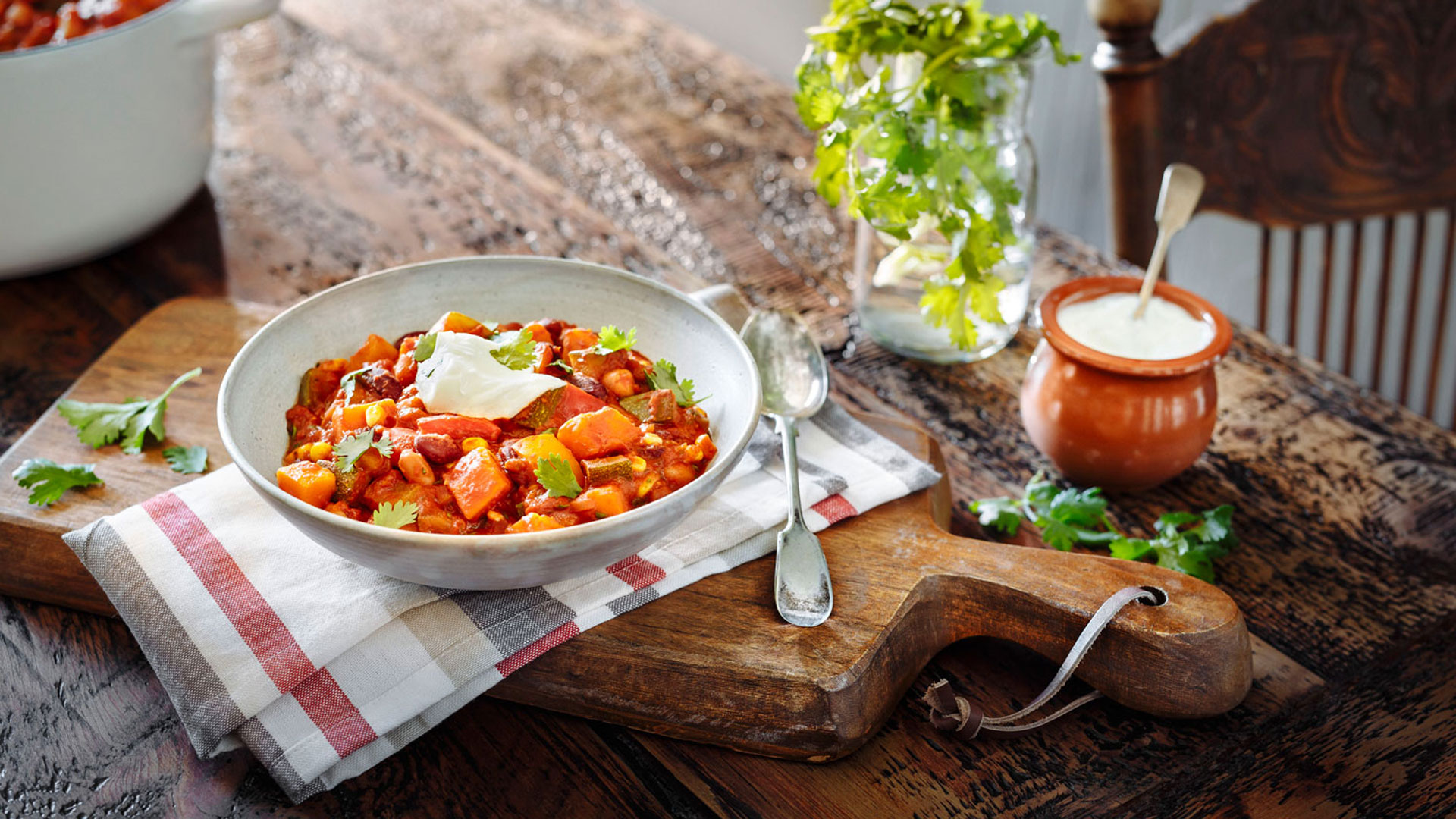 Bowl of vegetarian chili with sour cream on wooden cutting board