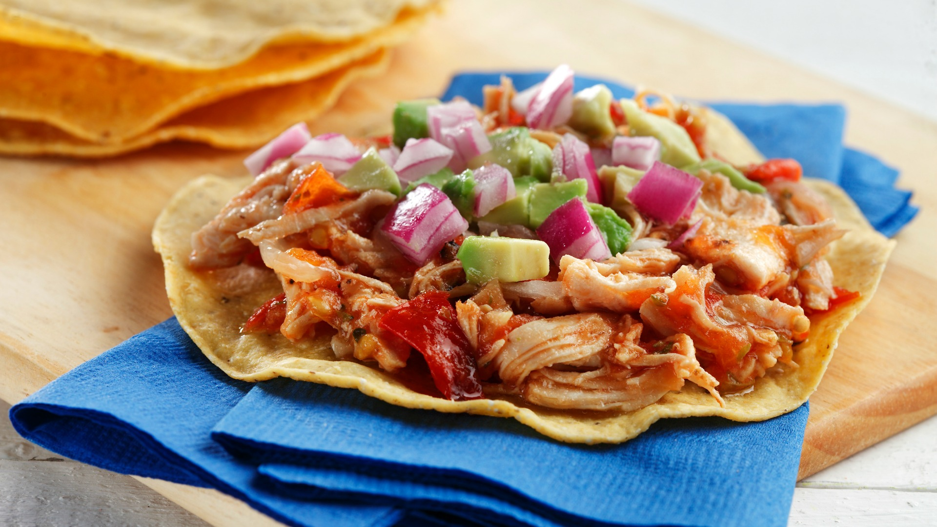 Shredded chicken tostadas with spicy tomato salsa on serving napkins