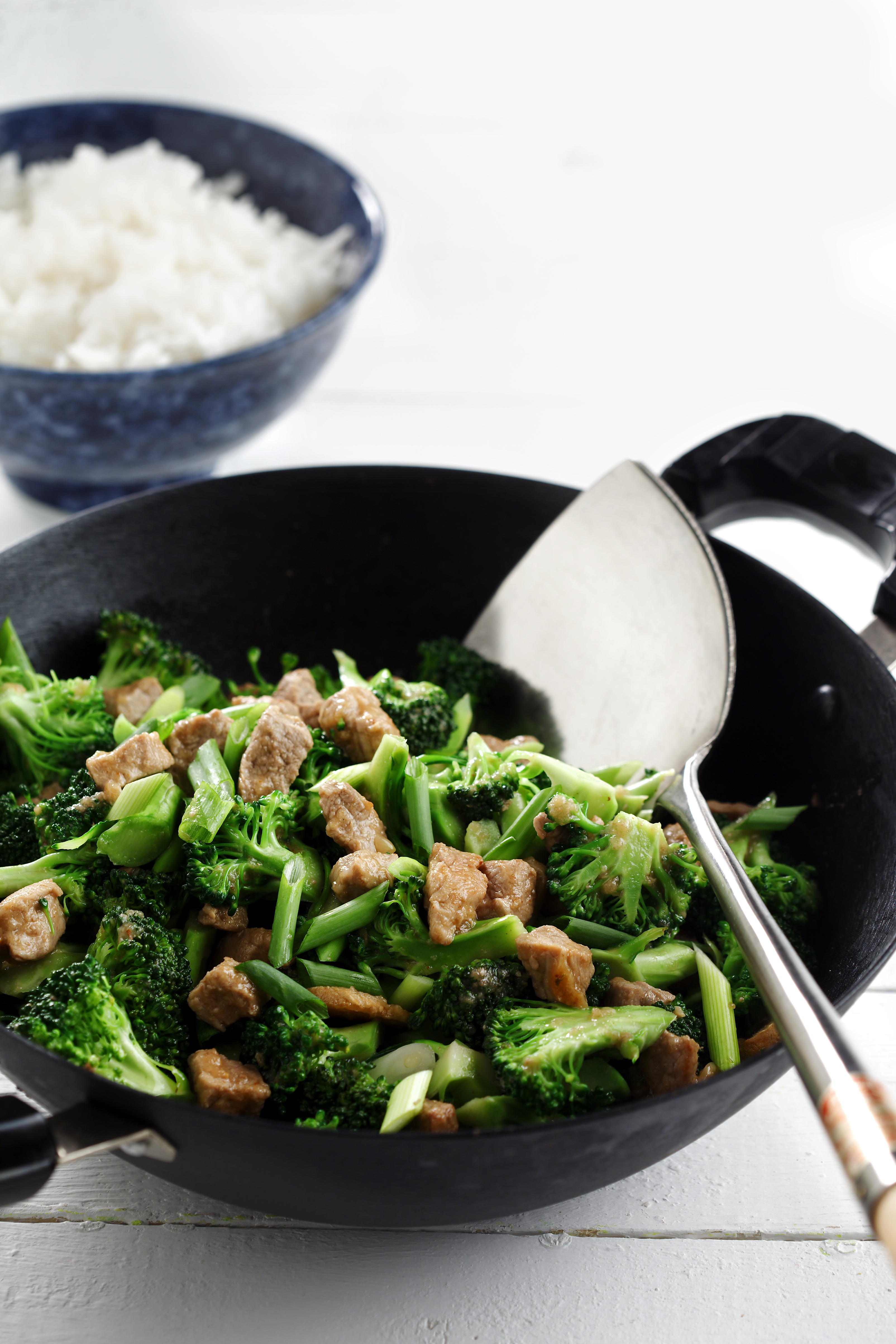 Stir-fried pork and broccoli with garlic-ginger sauce in a black wok