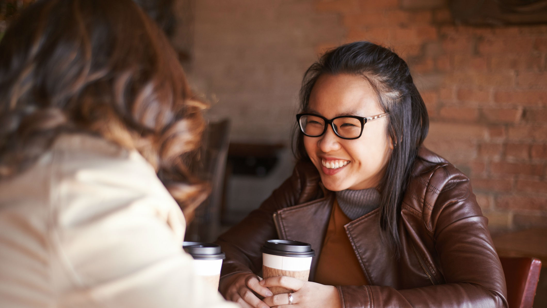 Woman smiling holding cup of coffee