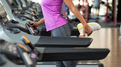 Woman stretching her legs on treadmill