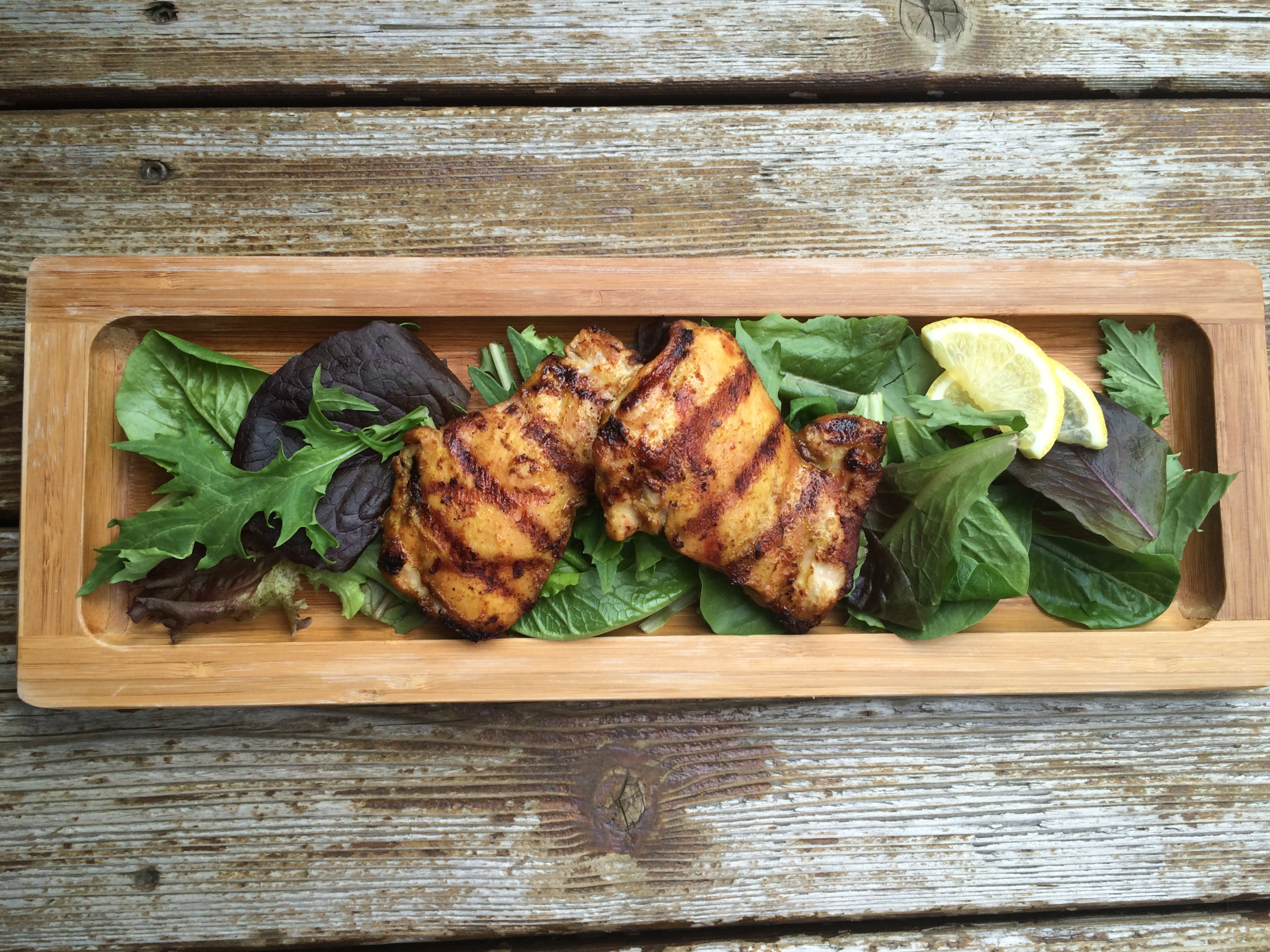 Zippy chicken thighs for the grill on a wooden plank.